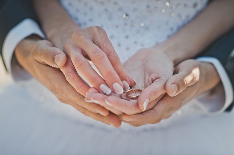 Mans and female hands hold wedding rings.